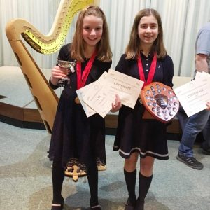Photo of two young harp players holding their awards